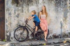 moeder en zoon op een fiets De openbare de Naamkinderen van de straatkunst op een fiets schilderden 3D op de muur die ` s twee kl Stock Foto's
