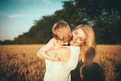 Moeder en zoon op een tarwegebied Stock Foto's