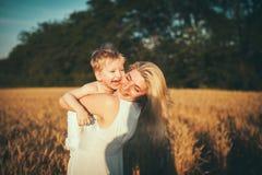 Moeder en zoon op een tarwegebied Stock Afbeeldingen