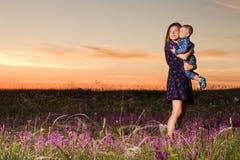 Moeder en zoon op zonsondergangachtergrond en gebied Royalty-vrije Stock Afbeelding