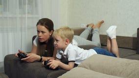 Moeder en zoons de spelen die van de spelcomputer met bedieningshendels op de laag liggen stock footage