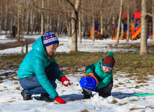Moeder en zoons het spelen met sneeuw Royalty-vrije Stock Afbeelding