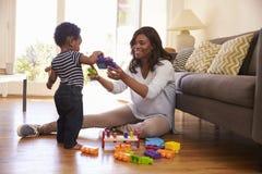 Moeder en Zoons het Spelen met Speelgoed op Vloer thuis Stock Afbeelding