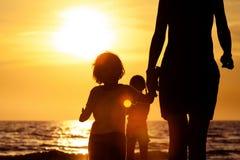 Moeder en zoons het spelen op het strand in de zonsondergangtijd Stock Afbeelding