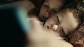 Moeder en zoons het spelen op tabletpc vóór bed stock videobeelden