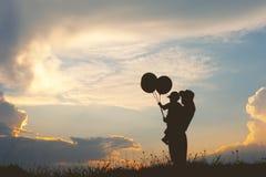Moeder en zoons het spelen in openlucht bij zonsondergangsilhouet Royalty-vrije Stock Foto's