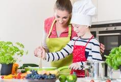Moeder en zoons kokend familiediner samen stock afbeeldingen