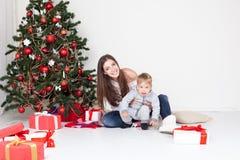Moeder en zoons open giften op Kerstmis en nieuw jaar royalty-vrije stock fotografie