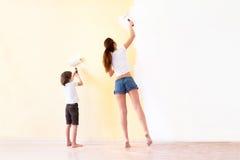 Moeder en zoons paiting muren in een nieuw huis stock afbeeldingen