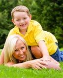 Moeder en zoons speelvoetbal in openlucht stock afbeeldingen