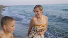 Moeder en zoonsdans op de kust Kust bij zonsondergang stock videobeelden