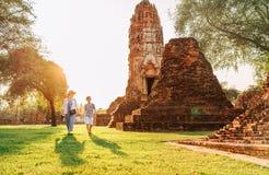 Moeder en zoonstoeristen die hand in hand in atcient Wat Chaiwatthanaram Buddhist-tempelruines lopen in heilige stad Ayutthaya, stock foto's