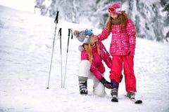 Moeder het bevestigen broek aan dochter op skiterrein Stock Foto