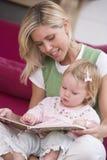 Moeder in het boek van de woonkamerlezing met baby