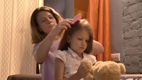 Moeder het borstelen haar van haar weinig dochter in moderne woonkamer, jong geitje het spelen met teddy, familieconcept binnen stock video