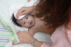 Moeder het drogende haar van haar leuke kleine baby Royalty-vrije Stock Afbeeldingen