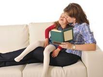 Moeder het kussen van en het vertellen sprookje aan leuk weinig dochter stock foto