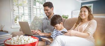 Moeder het letten op televisie terwijl vader en zoon die laptop en digitale tablet gebruiken royalty-vrije stock afbeeldingen
