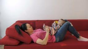 Moeder het spelen met baby` s voeten die op bank liggen stock footage