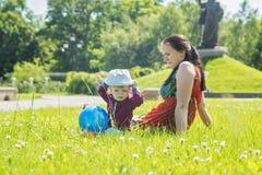 Moeder het spelen met haar baby op een grote zonnige dag in een weide met veel groen gras en wilde bloemen royalty-vrije stock afbeeldingen