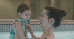 Moeder het spelen met haar babymeisje in de pool stock video