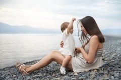 Moeder het spelen met haar dochter op het strand Stock Afbeeldingen