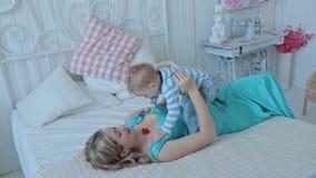 Moeder het spelen met haar zoon bij de slaapkamer stock videobeelden