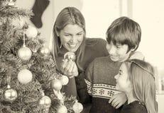 Moeder het spelen met kinderen met Kerstmisballen en boom Stock Foto