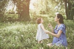 Moeder het spelen met weinig dochter in park Moeder en Stock Foto's