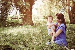 Moeder het spelen met weinig dochter in park Moeder en Stock Fotografie