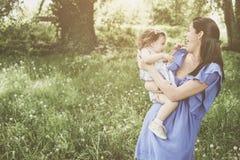 Moeder het spelen met weinig dochter in park Moeder en Stock Foto