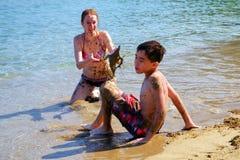 Moeder het spelen met zon met zand Stock Foto's