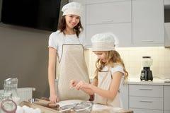 Moeder het stellen, het glimlachen, dochter kokende koekjes royalty-vrije stock foto's
