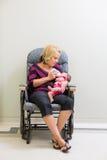 Moeder het Voeden Melk aan Pasgeboren Babymeisje op Stoel stock fotografie