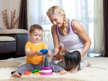 Moeder, kindjongen en huisdierenhond het spelen Stock Afbeeldingen