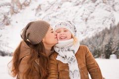 Moeder kussend kind in openlucht onder snow-capped bergen Royalty-vrije Stock Afbeelding