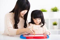 Moeder of leraar die kinddochter helpen aan het schrijven royalty-vrije stock foto
