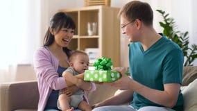 Moeder met baby die verjaardagsgeschenk geven aan vader stock footage