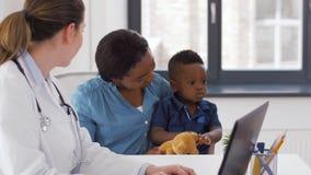 Moeder met baby en arts met laptop bij kliniek stock videobeelden