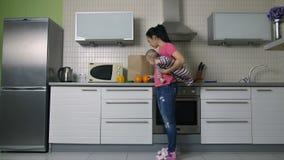 Moeder met baby het leegmaken het winkelen zak in keuken stock footage