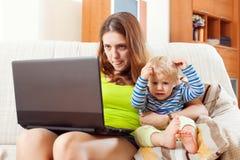 Moeder met baby het werken met laptop Stock Foto