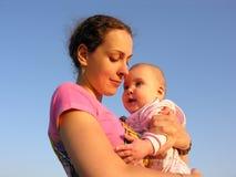 Moeder met baby onder hemel royalty-vrije stock afbeelding