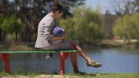 Moeder met baby op de bank door het meer stock videobeelden