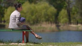 Moeder met baby op de bank door het meer stock footage