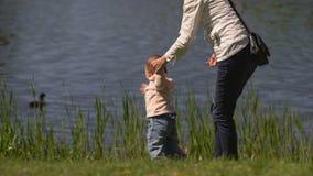 Moeder met baby op de kust van het meer stock footage