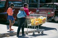 Moeder met baby op haar achter duwend boodschappenwagentje in Soweto royalty-vrije stock afbeelding