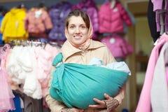 Moeder met baby in slinger bij winkel Royalty-vrije Stock Foto's
