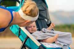 Moeder met baby in wandelwagen die van moederschap genieten bij zonsondergangland stock foto