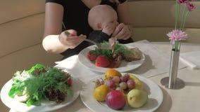 Moeder met babydochter die maaltijd in koffie hebben stock video