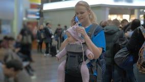 Moeder met babydochter het wachten bij de luchthaven, vrouw die op mobiel spreken stock videobeelden